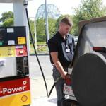 Kyle Downing of Dedham puts gas in his car at a Shell station in Sagamore Beach. Despite increases in recent months, summer gasoline prices are at a five-year low as drivers benefit from the boom in US oil production.