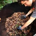Grant Berman adds red wiggler worms, which he breeds in his basement, to a leaf-and-cabbage composting mixture.