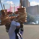 An Egyptian street vender selling bread walked past clashes near Cairo's Tahrir Square in 2013, as riot police fired a tear gas canister at protesters.