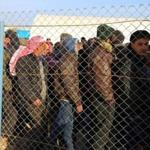 Syrians fleeing the conflicts in Azaz region, queue at the Bab al-Salam border gate on Friday.
