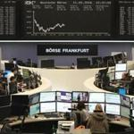 Traders worked in front of a board displaying the chart of Germany's share index DAX at the stock exchange in Frankfurt am Main, western Germany.