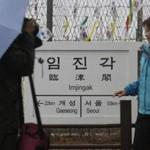 Tourists take their souvenir photos with a directional sign showing the distance to North Korea's Kaesong city and South Korea's capital Seoul at the Imjingak Pavilion near the border village of Panmunjom in Paju, South Korea, Friday, Feb. 12, 2016. South Korea has cut off power and water supplies to a factory park in North Korea, officials said Friday, a day after the North deported all South Korean workers there and ordered a military takeover of the complex that had been the last major symbol of cooperation between the rivals. (AP Photo/Lee Jin-man)