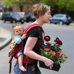 Carolyn Salvi of Somerville carried her daughter, Mohini, and some flowers that she got for herself for Mother's Day last year.