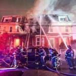 Firefighters battle a three-alarm fire on Rush Street in East Somerville.