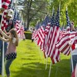 John Burrell of Dighton and his granddaughter, Nevaeh Keyes, helped the group Field of Honor erect 300 flags in recognition of fallen troops on the Mansfield Town Common. Rose Lincoln for The Boston Globe