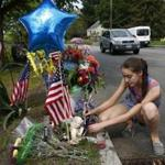 Shannon Courtney, 14, of Auburn, placed a pinwheel at a makeshift memorial where Officer Ronald Tarentino was killed.