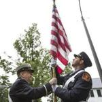 Lieutenant Brian Doherty (left) and Firefighter Patrick Muse unfurled an American flag in Milton.