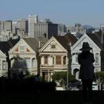 "A woman looked toward the ""Painted Ladies,"" a row of historic Victorian homes, with the San Francisco skyline in the background."