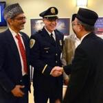 The Ahmadiyya Muslim Community of Boston hosted an Iftar dinner with a reception, guest speakers, and an introduction to Islam at the Sharon Community Center. From left to right, Dr. Amer Malik, Sharon police Lieutenant Donald Brewer, and Nasir Rana greet one another.