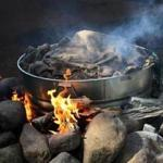 A roaring fire heats a burlap-covered steel tub filled with lobsters, clams, corn, potatoes, sausages, and more.