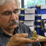 Robert Megerdichian looks over a miniature Hoover vacuum cleaner crafted by his father.
