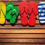 Multicolor flip-flops on wooden background. Summer family vacation concept; Shutterstock ID 269437022; PO: oped