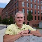 Lowell City Councilor Rodney Elliott in front of the Lofts at Perkins Park, an apartment complex that was recently bought by UMass-Lowell, thereby removing it from city tax rolls