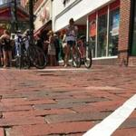 Students used white tape to create lanes on the sidewalk intended to keep texting pedestrians from collisions.