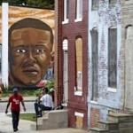 FILE - In this June 23, 2016 file photo, a mural depicting Freddie Gray is seen past blighted row homes in Baltimore, Thursday, June 23, 2016, at the intersection where Gray was arrested. Gray later died in police custody. An Associated Press review of court records nationwide shows that the attorneys who represent cities are sometimes weak links in the systems meant to hold police accountable for wrongdoing. The review found that lawyers deliberately hid important facts, delayed their disclosure or otherwise sought to subvert evidence in civil cases. (AP Photo/Patrick Semansky, File)