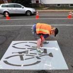 Sarah Lee painted a sign on a temporary bike lane on Maynard's Main Street this summer.