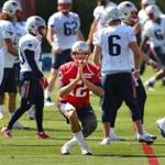 Quarterback Tom Brady looked like he was doing a yoga stance as he loosens up during the first day of Patriots training camp.