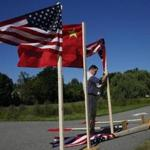 A worker reset several flags after winds toppled them at Busche Academy.