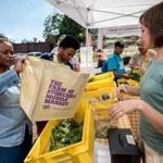Angela Beyer (right) helps out a customer at Stonehill College's Mobile Market in Brockton.