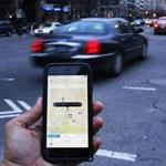 (FILES) This file photo taken on March 25, 2015 shows an UBER application shown as cars drive by in Washington, DC. The US ride-sharing service Uber announced August 18, 2016 it had acquired the commercial transport-focused tech startup Otto as the company presses ahead with its pursuit of self-driving technology. The announcement came as the company also announced a $300 million effort with the Sweden-based automaker Volvo Cars to develop driverless cars.