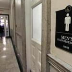 Visitors walked past a men's bathroom while exiting the State House in Boston earlier this year.