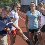 Whitman-Hanson soccer coach David Fleck checks his notes while star players Taylor Kofton, Lauren Bonavita, and Katie Korzec prepare for a two-mile conditioning run.