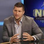 FILE - In this Aug. 6, 2014, file photo, Tim Tebow answers a question during a interview on the set of ESPN's new SEC Network in Charlotte, N.C. Tebow will be featured at the Republican National Convention in Cleveland next week. Tebow will be there. Tom Brady will pass. (AP Photo/Chuck Burton, File)