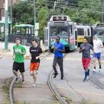 A group of runners began their race against an MBTA Green line train along Commonwealth Avenue in Boston.