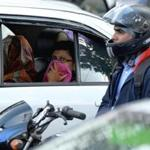 An Indian commuter protected her face from dust and pollution at a busy traffic junction in Bangalore Tuesday.