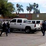 A video still frame provided by the El Cajon Police Department, a man, second from left, faced police officers in El Cajon, Calif. The man reportedly acting erratically at a strip mall in suburban San Diego was shot and killed by police.