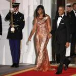 President Barack Obama and first lady Michelle Obama walk to North Portico at the White House in Washington, Tuesday, Oct. 18, 2016, to greet Italian Prime Minister Matteo Renzi and his wife Agnese Landini, for a State Dinner. The first lady is wearing a floor length, rose gold chainmail gown designed by Atelier Versace. (AP Photo/Manuel Balce Ceneta)