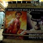 A man stands in a DVD shop in Rawalpindi, Pakistan, near a display of Bollywood movies.