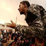 An Iraqi soldier tried to calm displaced people who were seeking food at a processing center in Qayyara, Iraq, on Sunday.