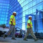 Workers passed by the new Mohegan Sun Hotel, which reflected the original hotel. The new facility is expected to open next month.