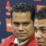 Boston Red Sox director of international scouting Eddie Romero (L) listens as Cuban baseball player Yoan Moncada speaks to reporters at the Boston Red Sox training complex in Fort Myers, Florida March 13, 2015. Moncada and the Red Sox announced a record $31.5 million deal after he passed a pending physical, according to team officials on Friday. REUTERS/Steve Nesius (UNITED STATES - Tags: SPORT BASEBALL)