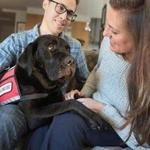 Jessica Kensky and her husband, Patrick Downes, play with Rescue, a service black Labrador.