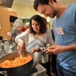 Instructor Shruti Mehta helps Kim Winniker of Brookline as he makes sweet potato bharta during a class on Indian vegetarian cooking.