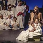 "Kaleisha Chance, as Mary, holds Logan Watson (baby Jesus), while Derek Louizia (Joseph) and members of Black Persuasion look on in ""Black Nativity,"" presented by National Center of Afro-American Artists."
