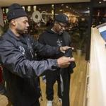 "Kareem ""Biggs"" Burke (left) and Emory Jones check out clothing from the Roc96 Capsule Collection commemorating the 20th anniversary of Jay-Z's album ""Reasonable Doubt"" at Concepts in Harvard Square."