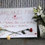 Signs and flowers adorned a fence near the site of a warehouse fire in Oakland, Calif.