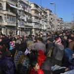 Syrians fleeing the violence in Aleppo gathered at a checkpoint Thursday manned by progovernment forces in the city.