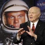 FILE - In this Feb. 20, 2012, file photo, U.S. Sen. John Glenn talks with astronauts on the International Space Station via satellite in Columbus, Ohio. Changing Port Columbus' name to John Glenn Columbus International Airport will cost an estimated $775,000 in new signs, according to a newly released study. The airport was named in honor of the astronaut and former U.S. senator in June 2016. The 95-year-old Ohio native was the first American to orbit the earth. (AP Photo/Jay LaPrete, File)