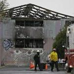 A pair of Oakland fire officials walk past the remains of the Ghost Ship warehouse fire Wednesday, Dec. 7, 2016, in Oakland, Calif. The fire that killed 36 people during a party at an Oakland warehouse started on the ground floor and quickly raged, with smoke billowing into the second level and trapping victims whose only escape route was through the flames, federal investigators said Wednesday. (AP Photo/Eric Risberg)