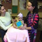 22zobella - Dr. Laura Scharf of Quincy Pediatrics discusses the importance of reading to Lesley Vargas as her baby, Adela, investigates her new book. (Bella English)