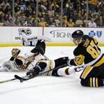 Penguins forward Sidney Crosby (87) was on his knees but still tried to put the puck past Bruins defenseman Torey Krug (47) and goalie Tuukka Rask.