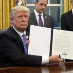 President Donald Trump held up the executive order withdrawing the US from the Trans-Pacific Partnership on Monday.