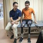 Earlier this month, prosthetist David Rotter (left) of Scheck & Siress coached Vidal Lopez before he took a walk down the hallway in his new prosthetic legs.