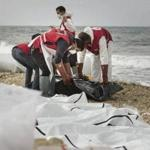 A handout photo made available by the Libyan Red Crescent showed volunteers of the Red Crescent as they recovered bodies that washed ashore at the coast near Al Zawiya, Libya, on Monday.