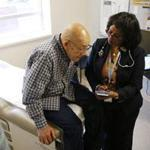 Frias Radhame, 76, a tuberculosis patient at Lynn Community Health Center, consulted Dr. Hanna H. Haptu.