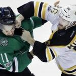 Boston Bruins defenseman Kevan Miller (86) punches Dallas Stars left wing Curtis McKenzie (11) during the second period of an NHL hockey game in Dallas, Sunday, Feb. 26, 2017. (AP Photo/LM Otero)